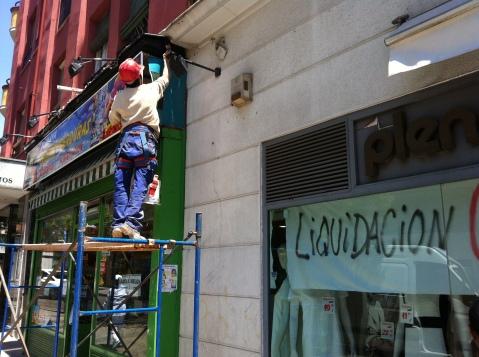Imagen de un obrero que está ultimando los detalles de la fachada de un nuevo establecimiento de productos latinoamericanos en la avenida de Monte Igueldo de Madrid, en el distrito de Puente de Vallecas