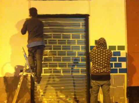 grafiteros trabajan en la calle Monte Igueldo pintando el exterior de un nuevo negocio de moda